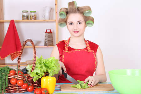 beautiful woman cutting salad in the kitchen photo