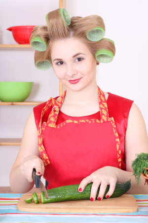 young attractive housewife cutting cucumber in the kitchen Stock Photo - 17419729