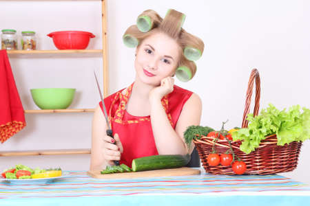 young attractive woman cutting cucumber in the kitchen Stock Photo - 17419750