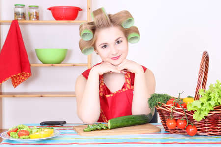young beautiful woman cutting cucumber in the kitchen Stock Photo - 17419736