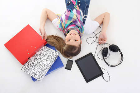 beautiful teenage girl lying with tablet pc, phone and headphones photo