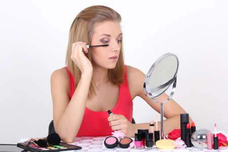 young beautiful woman with make up accessories and mirror photo
