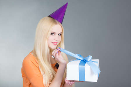 portrait of young beautiful woman with gift over grey photo