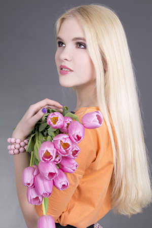 portrait of beautiful blondie girl with pink tulips over grey photo