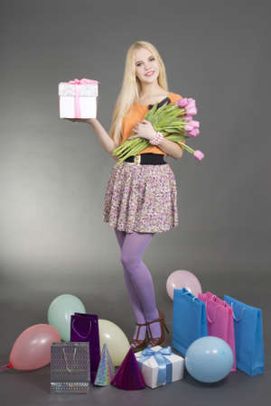 portrait of beautiful blondie girl with gifts and pink flowers photo