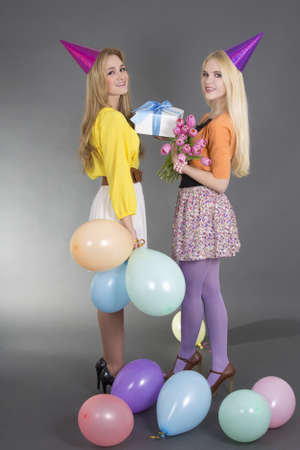 beautiful girls with gifts at a birthday party over grey photo