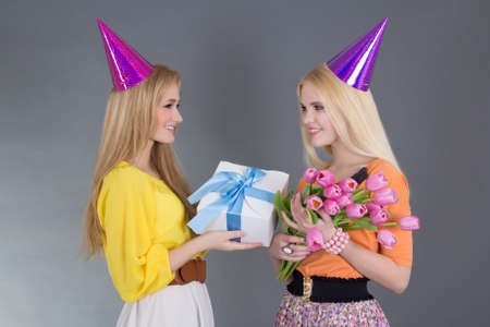 attractive girl giving a present and flowers to her friend photo