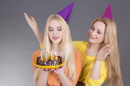 teenage girls with birthday cake over grey background photo