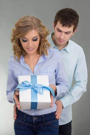 young attractive couple with gift over grey photo