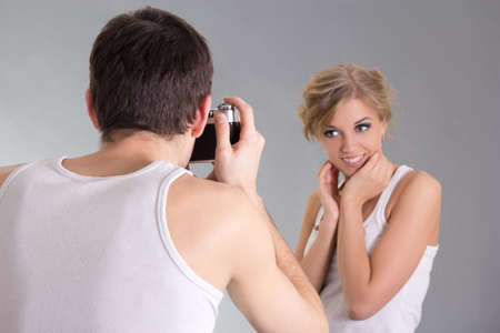 photographer and young attractive woman posing over grey photo