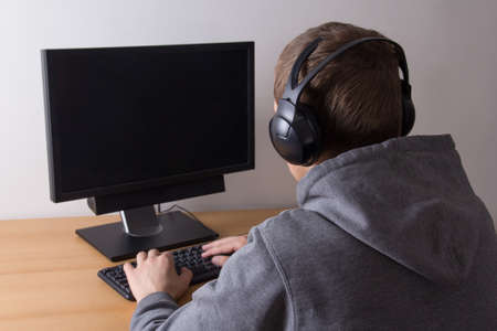 young man using a pc and listening music photo