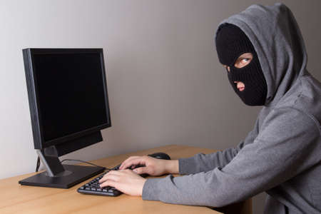 young masked hacker using a computer Stock Photo - 18359499