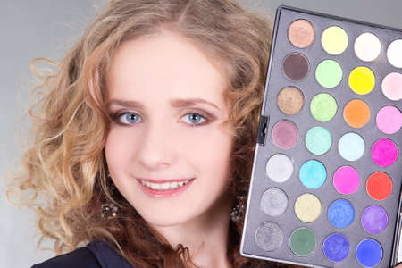 young beautiful woman with make up palette over grey photo