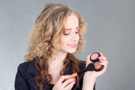 young attractive make up artist with brush over grey background photo