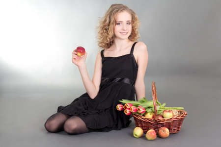 young blond sitting with apples and tulips photo