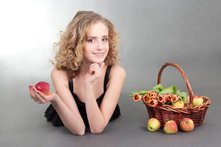 young blond lying with apples and tulips photo