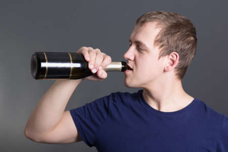 young man drinking champagne over grey background photo