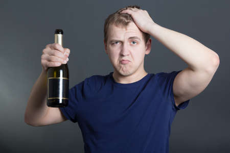 drunk man with bottle of champagne over grey background photo