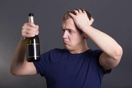 joven borracho con una botella de champán sobre fondo gris Foto de archivo