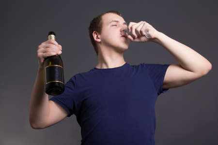 man drinking champagne over grey background photo