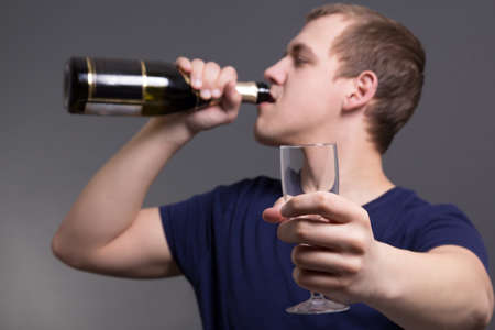 man drinking alcohol over grey background photo