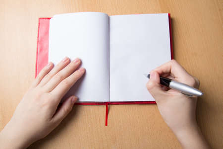 female hands with pen and notebook on desk Stock Photo