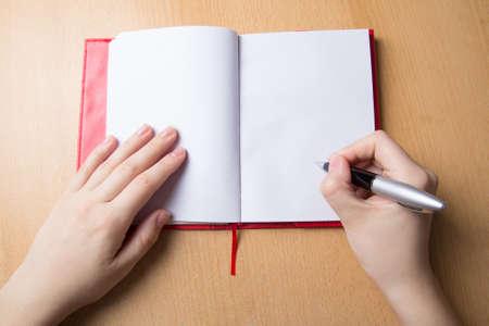 escribiendo: manos femeninas con la pluma y el cuaderno en el escritorio