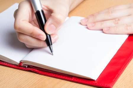 writers: hand of young woman taking notes in notebook Stock Photo