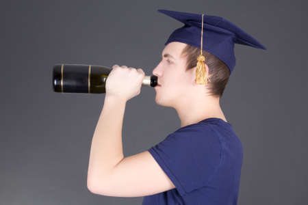 graduation man drinking champagne over grey background Stock Photo - 18498997