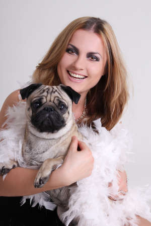 portrait of young woman with pug dog over grey photo