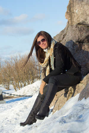 portrait of attractive brunette with sunglasses in winter park photo