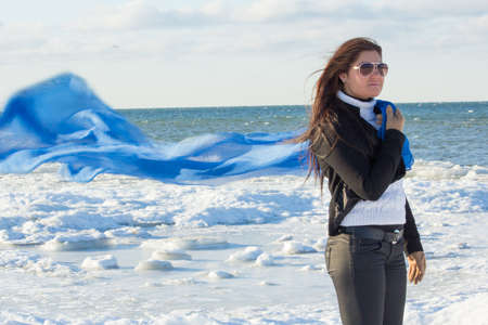 portrait of young attractive woman with scarf on winter beach photo