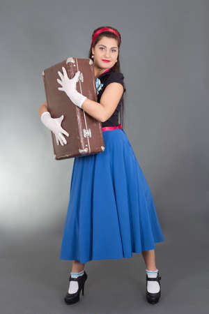 young beautiful pinup girl with retro suitcase over grey photo