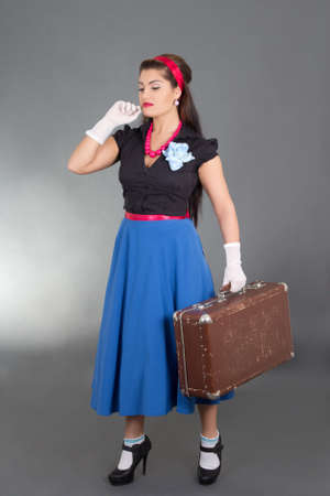 young attractive pinup woman with retro suitcase over grey photo