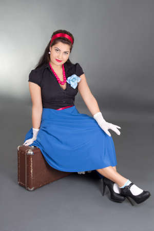 young attractive pinup woman sitting on retro suitcase over grey photo