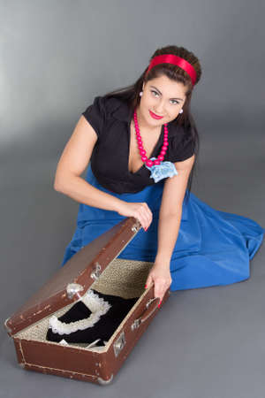 young beautiful pinup girl packing retro suitcase over grey photo