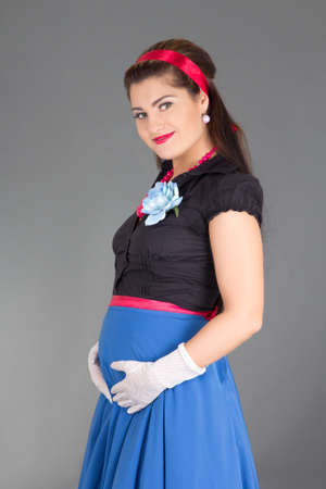 young pregnant woman in retro clothes over grey photo