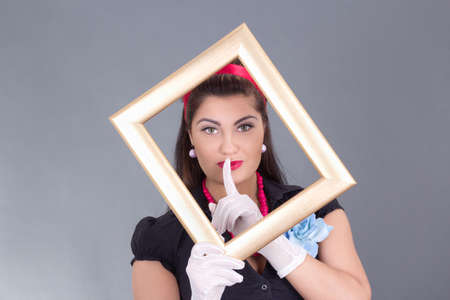 pinup girl with a frame around her face and finger on lips over grey photo