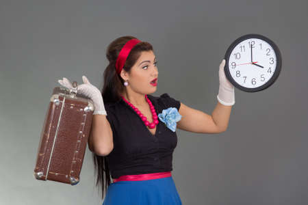 amazed beautiful pinup woman with suitcase and clock over grey photo