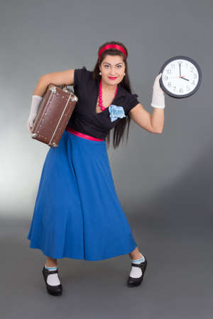 beautiful pinup woman with retro suitcase and clock over grey photo