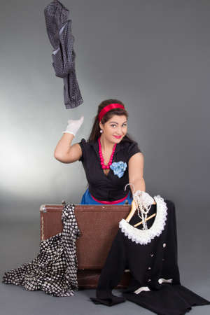 funny pinup girl packing her retro suitcase photo