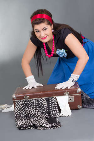 funny pinup girl with overfilled suitcase over grey photo