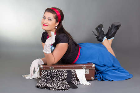 funny pinup girl lying on overfilled suitcase over grey photo