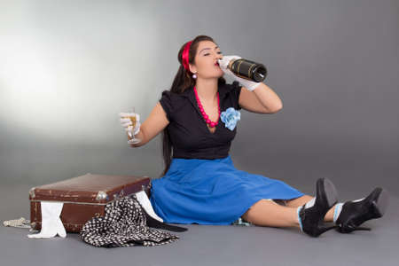 funny pinup girl drinking champagne and overfilled suitcase over grey photo