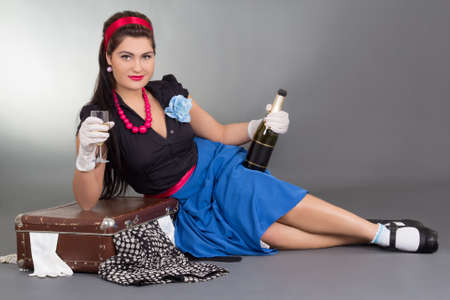 over packed: pinup girl with bottle of champagne and packed suitcase over grey