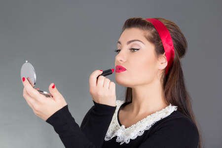 pinup woman with little mirror putting red lipstick photo