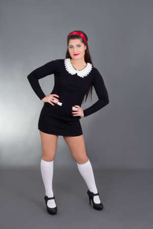 sexy schoolgirl: sexy maid in black uniform over grey Stock Photo