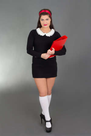 sexy schoolgirl with red folder over grey photo