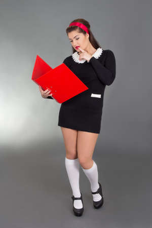 picture of sexy woman in school form with red folder over grey photo