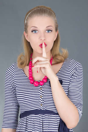attractive pinup girl in striped dress with finger on her lips Stock Photo - 18960998